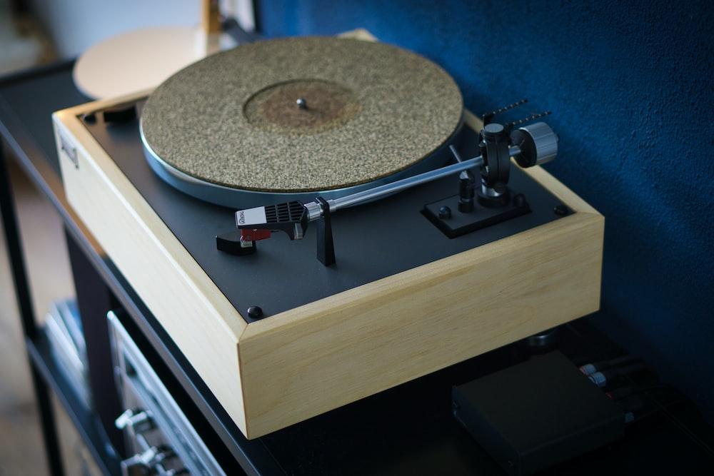 beige turntable on black wooden table