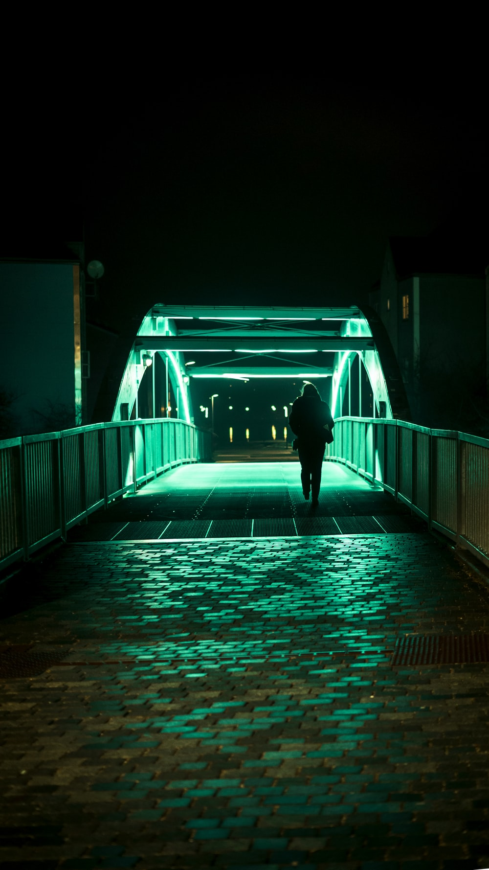 person passing alone on bridge during nighttime