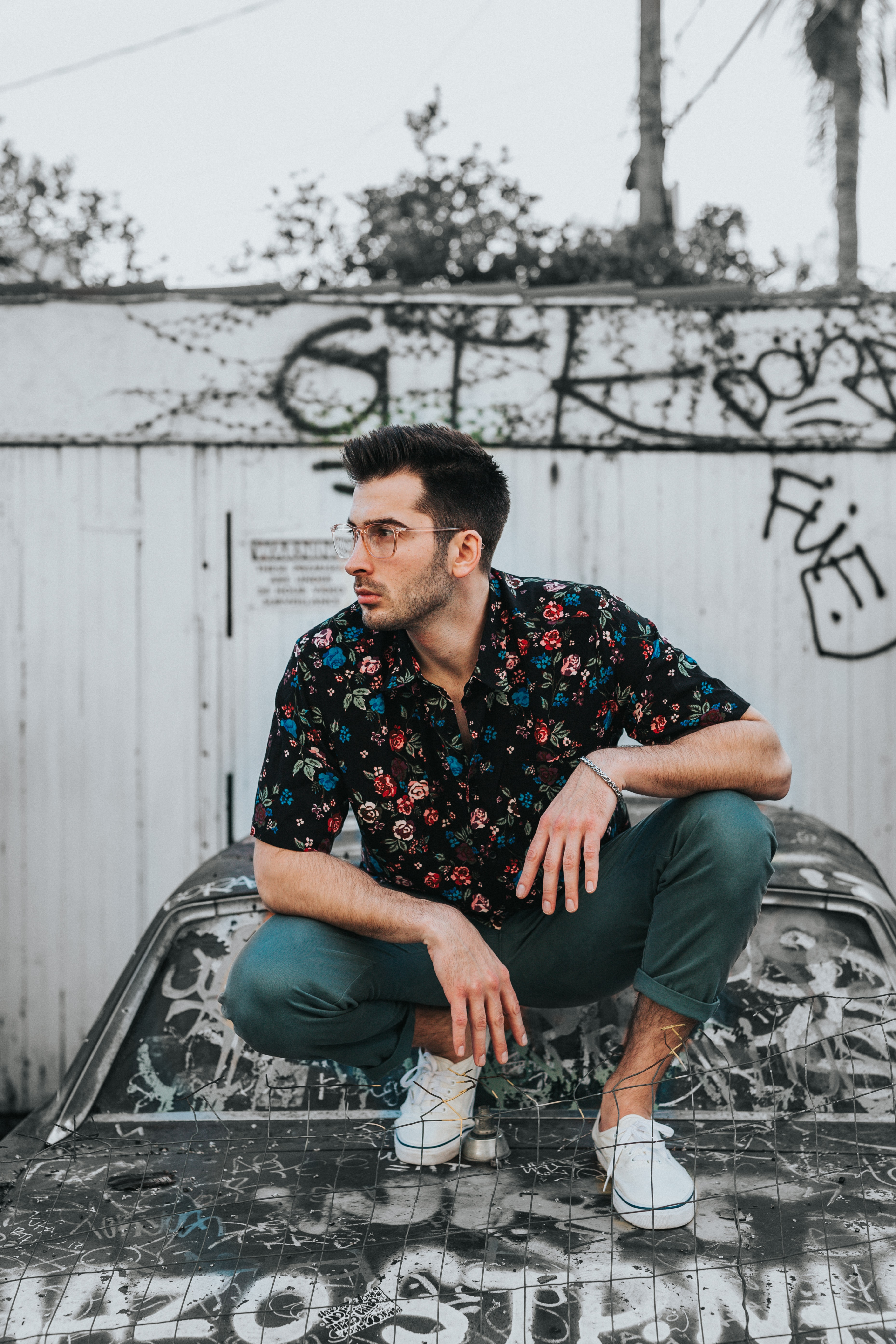 man in black, blue, and red floral button-up collared shirt and gray pants sitting on car hood during daytime