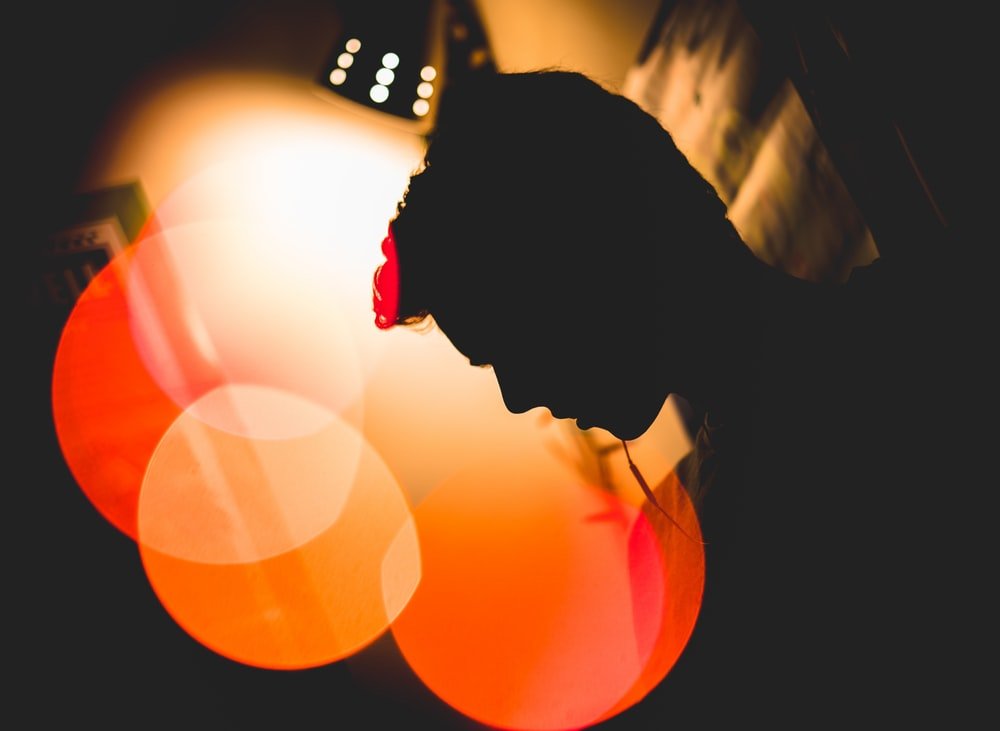 bokeh photography of silhouette of man leaning on wall