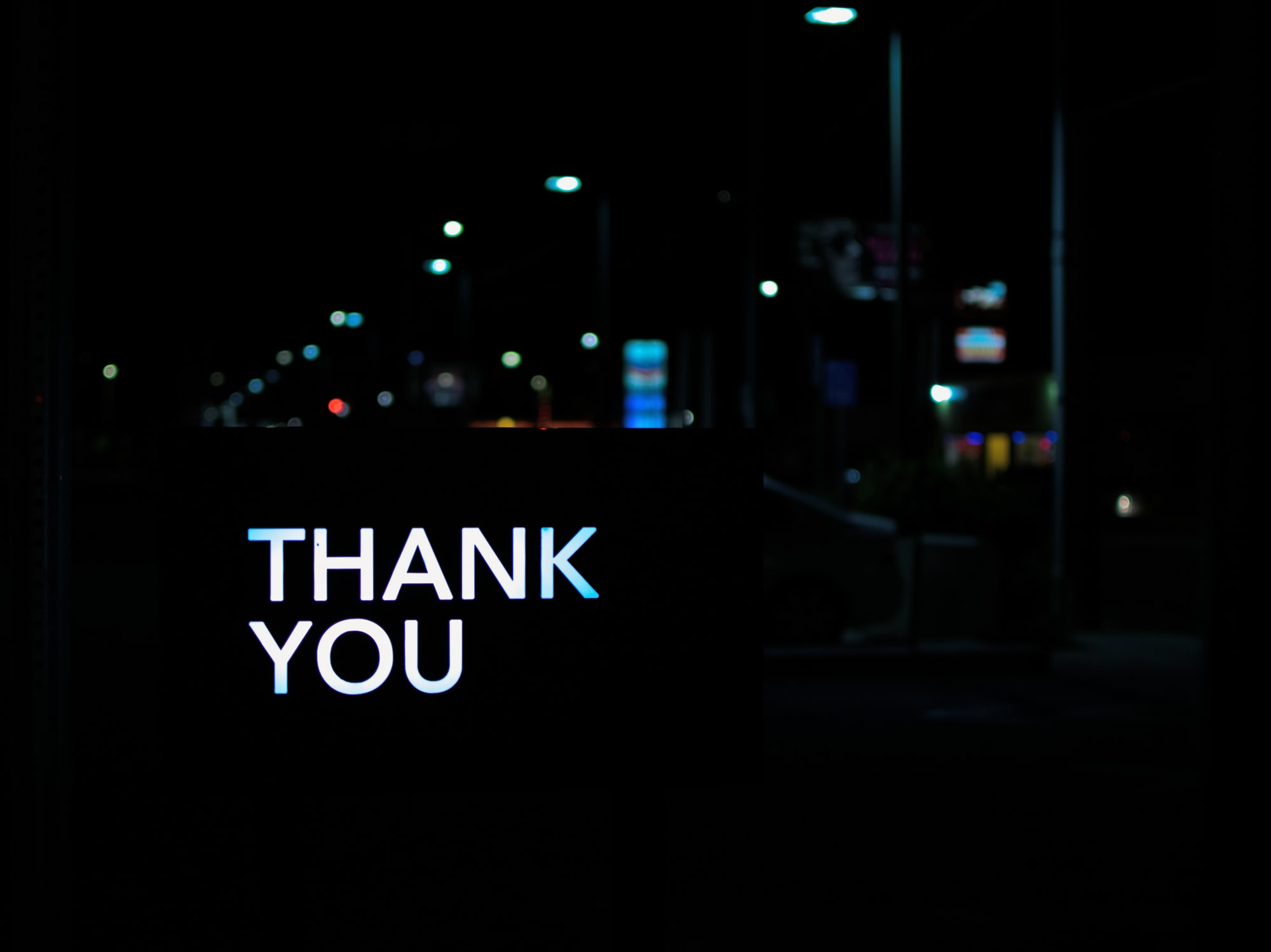 """The words """"thank you"""" light up the night on a darkened city street."""