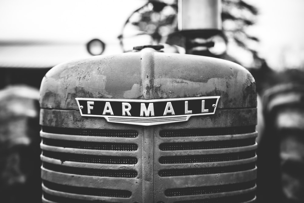 grayscale photo of Farmall tractor during daytime