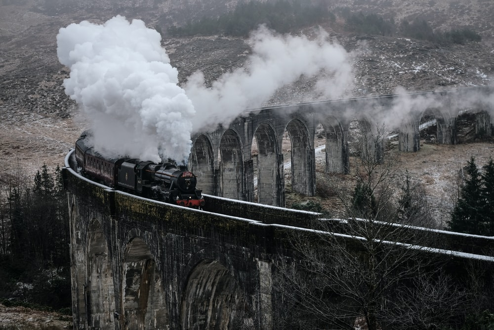 black steam train emitting smoke on concrete railway during daytime