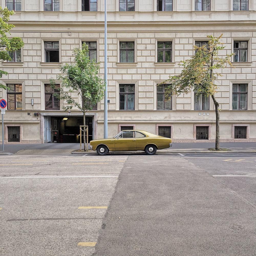 yellow sedan on concrete roadway