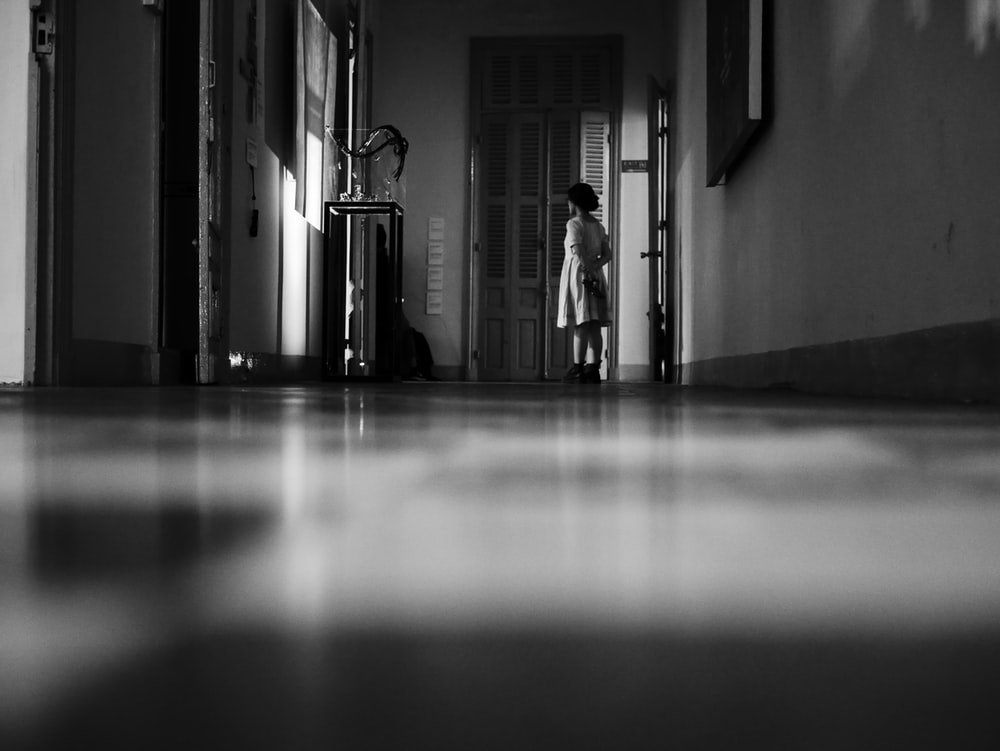 grayscale photo of woman standing near wall and open door