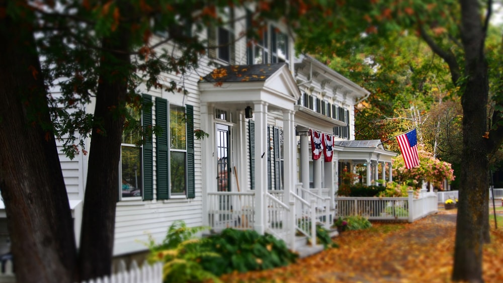 white and gray wooden house with US flag