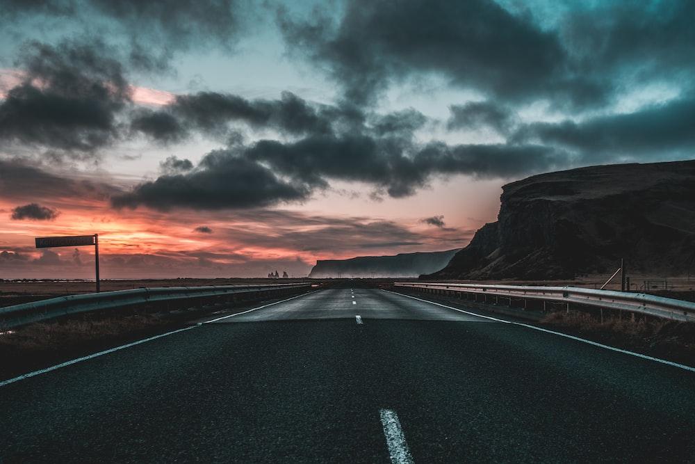 road under dark clouds during sunset