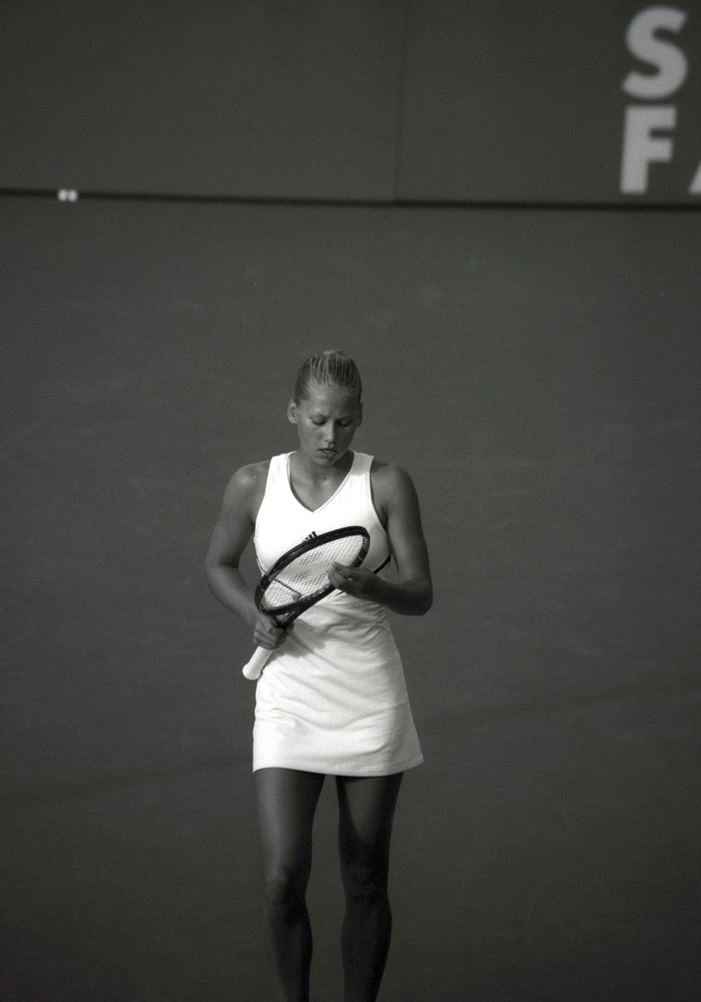 woman wearing dress holding tennis racket