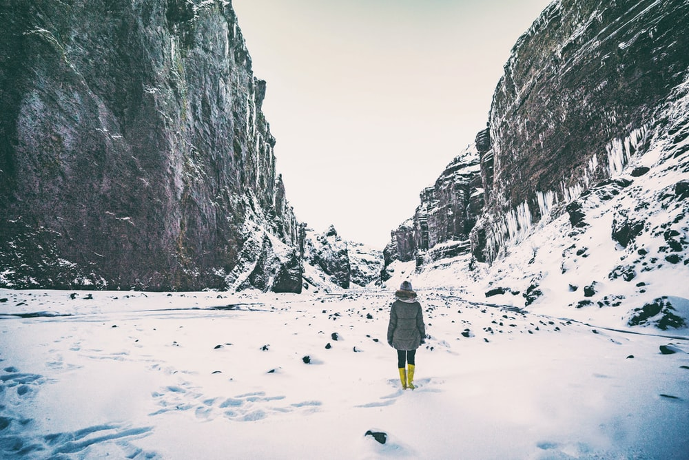woman wearing gray coat standing in between mountain coated by snow