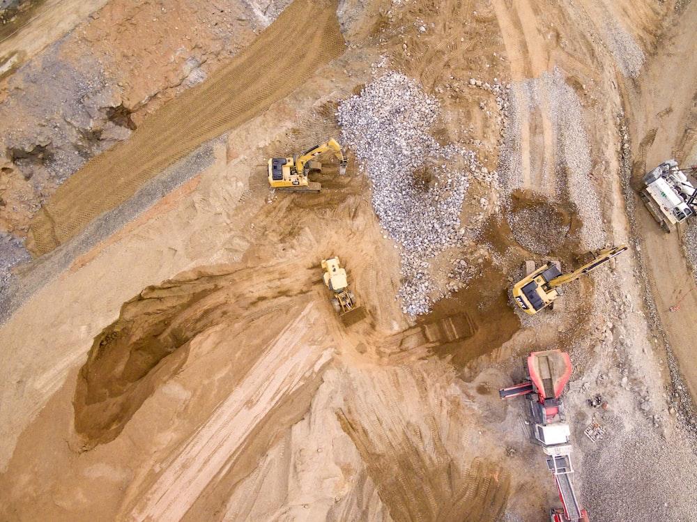 aerial photography of three heavy equipment