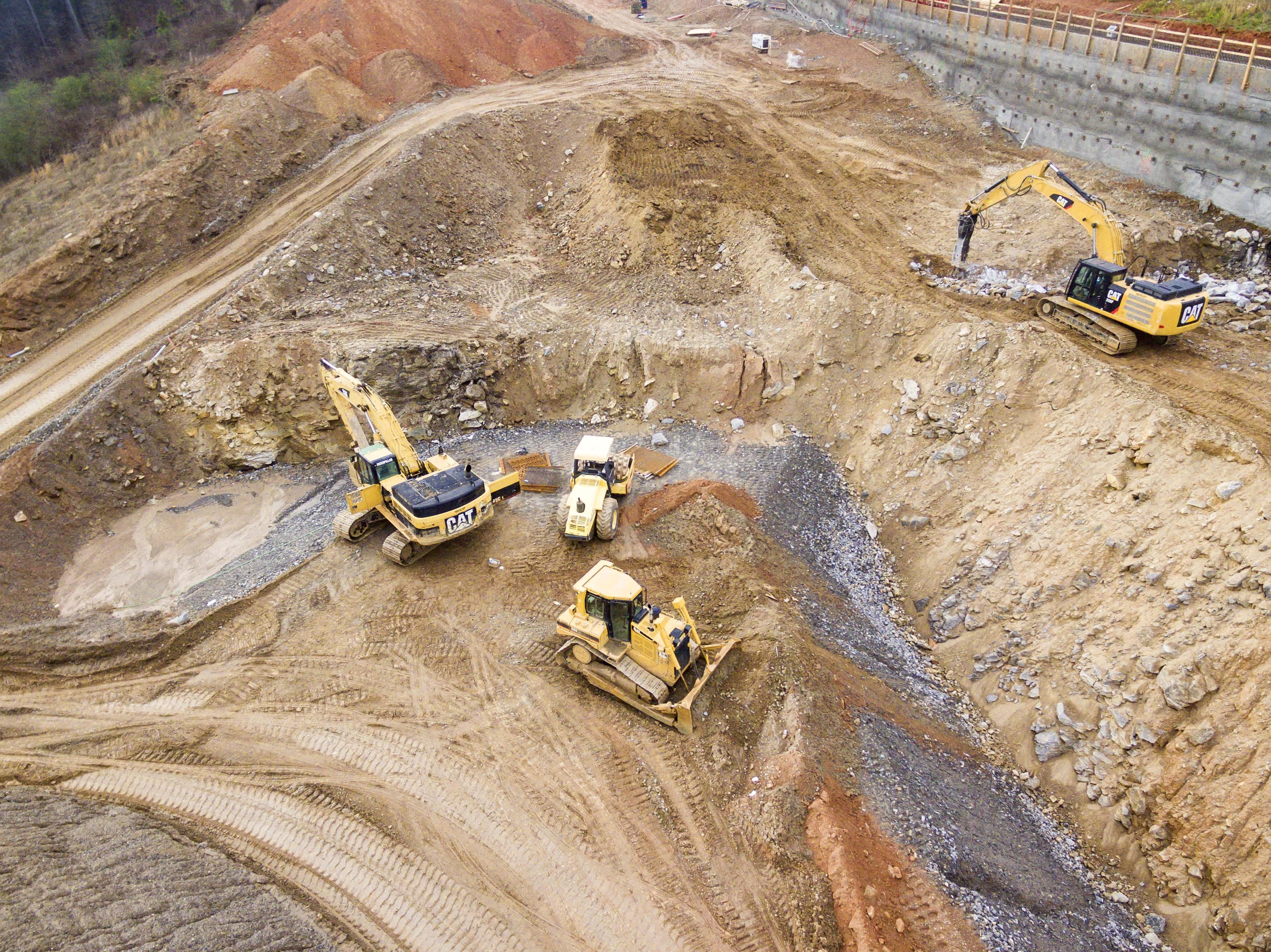 top view photography of four heavy equipment on quarry at daytime