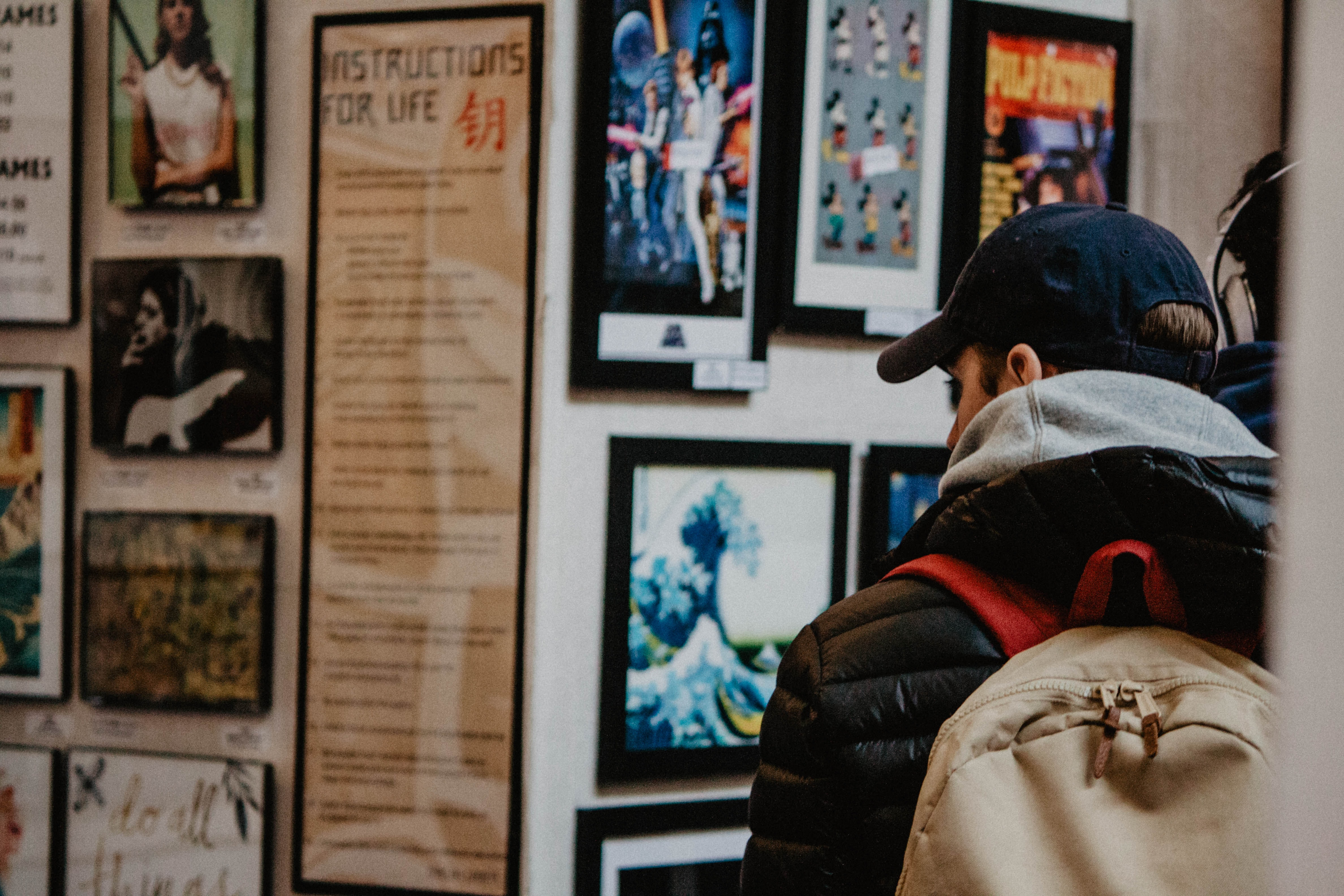 person wearing black bubble jacket watching wall posters