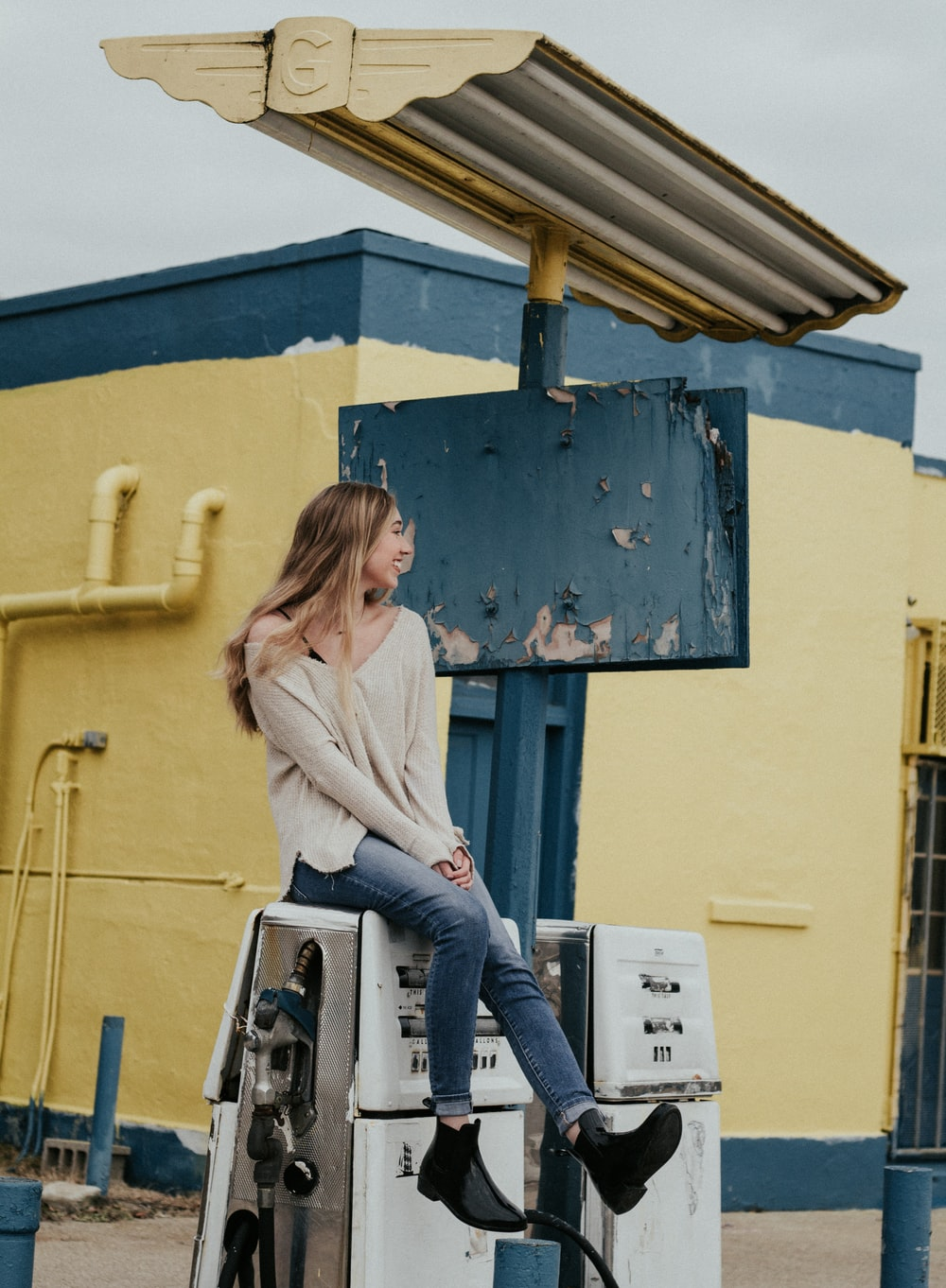 woman sitting on white gasoline pump machine during daytime