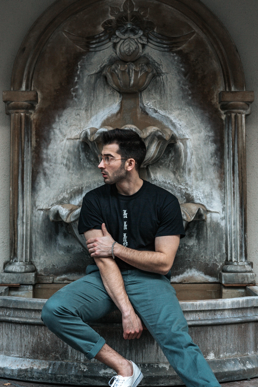 man wearing black shirt sitting near the fountain
