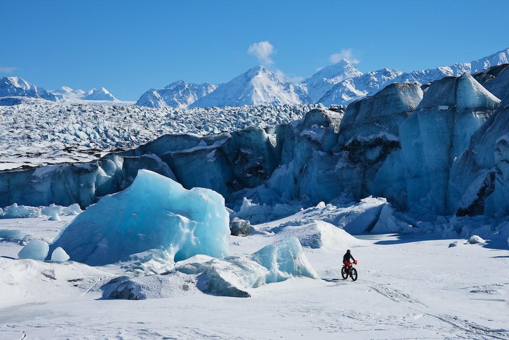 man using bicycle on snow