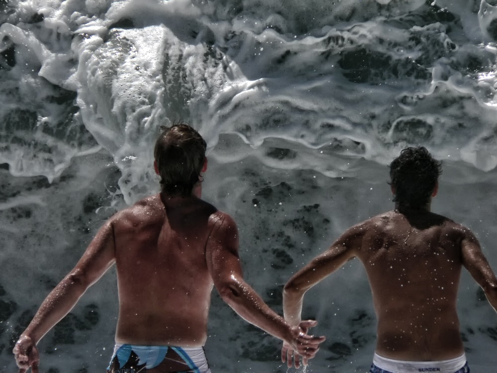 two person in front of wave