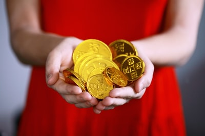 person holding gold-colored ching coins lunar new year teams background