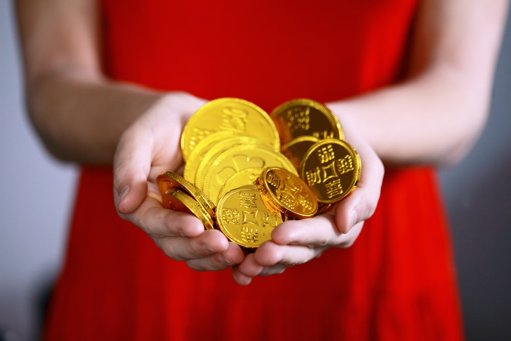 person holding gold-colored ching coins