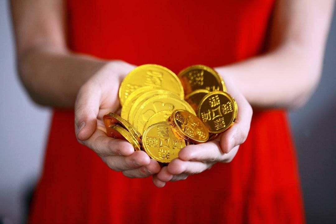 Mujer muestra un puñado de monedas de oro