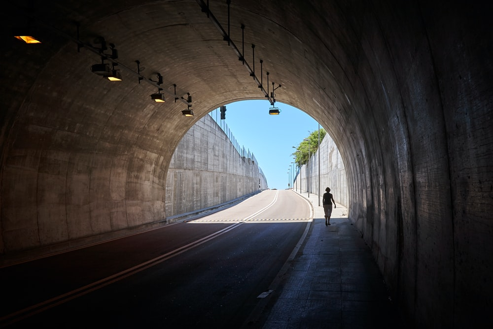 photo of person walking under tunnel