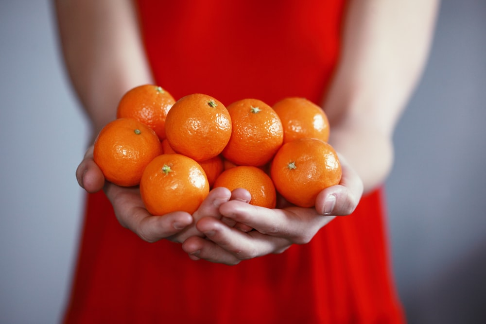 person holding orange fruits