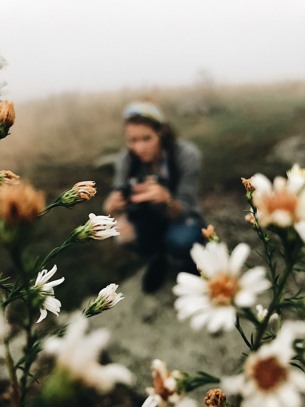 shallow focus photo of woman and flowers