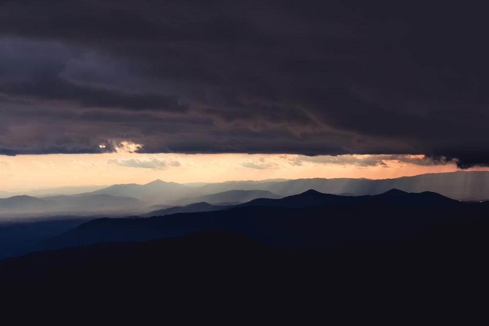 mountain range under cloudy sky