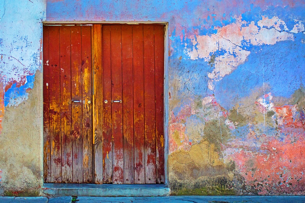 red wooden door of blue, red, and brown painted wall