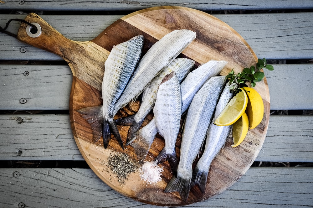 headless fishes with sliced of lemons on brown wooden chopping board