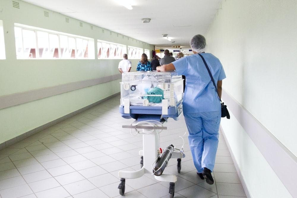 person walking on hallway in blue scrub suit near incubator