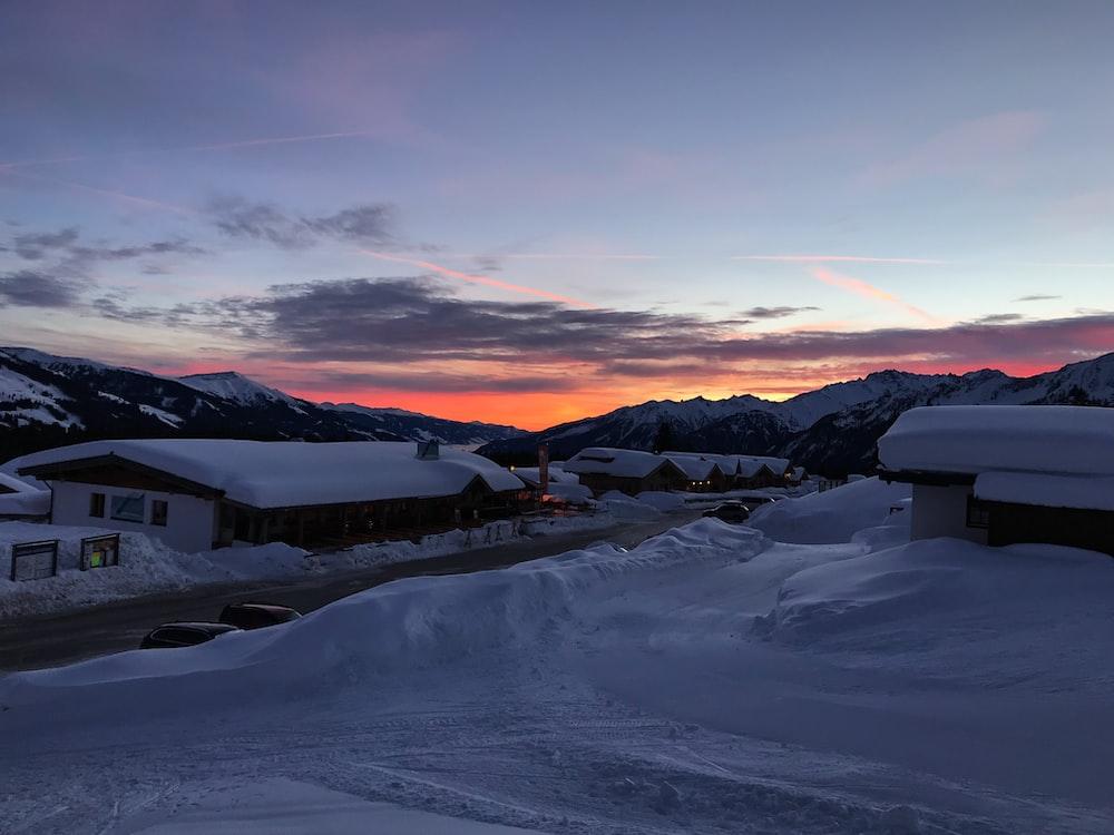 snow covered house near mountain under blue sky