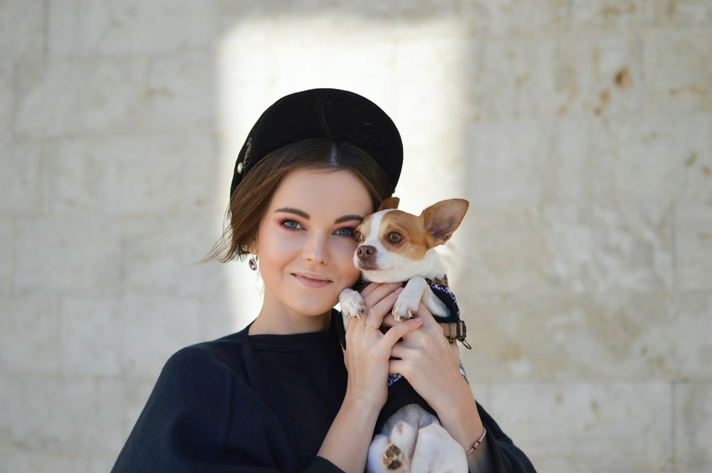 portrait photo of woman carrying puppy