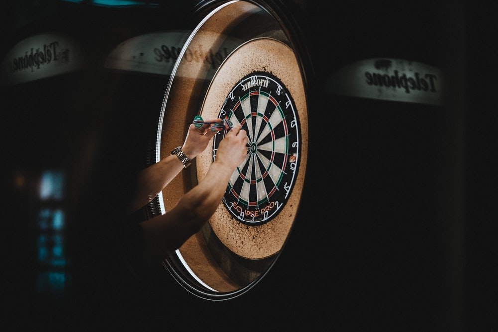 person picking dart pins on board