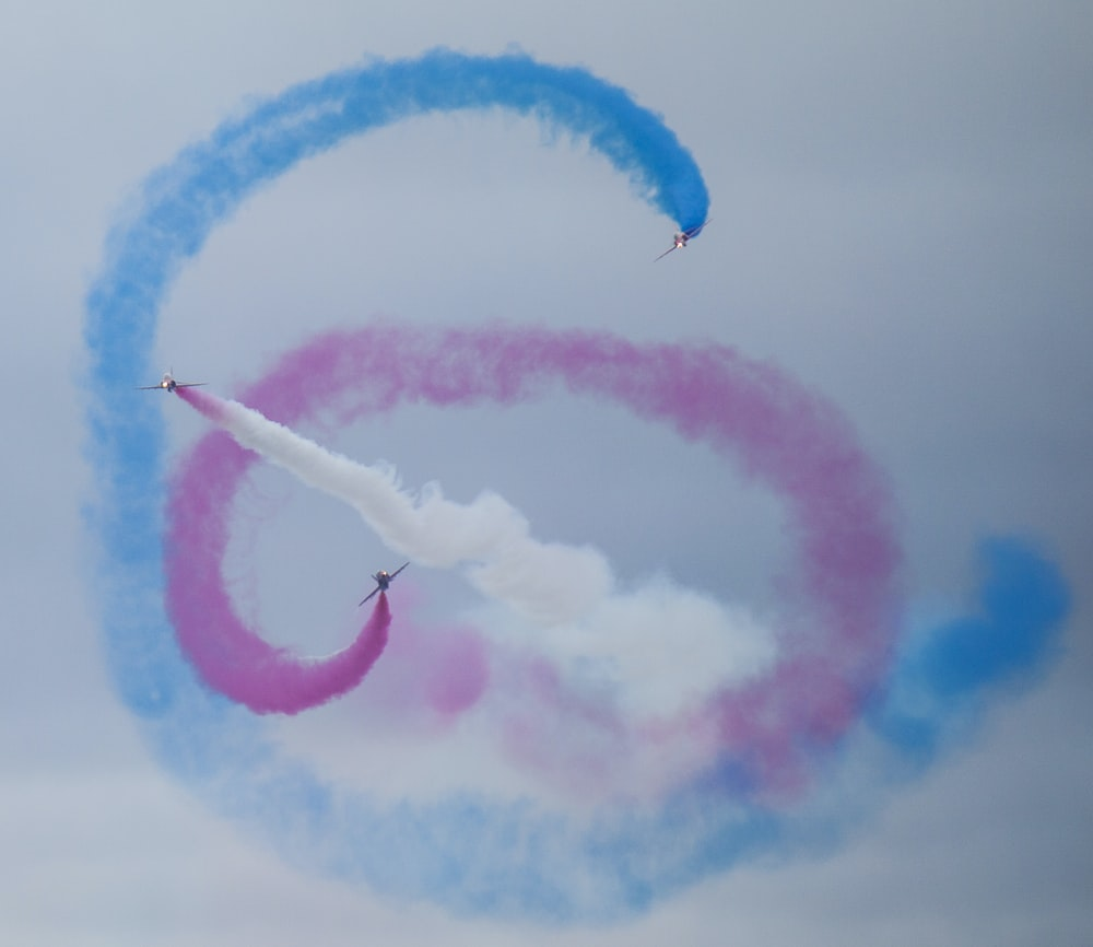 blue, white, and pink smokes under blue sky