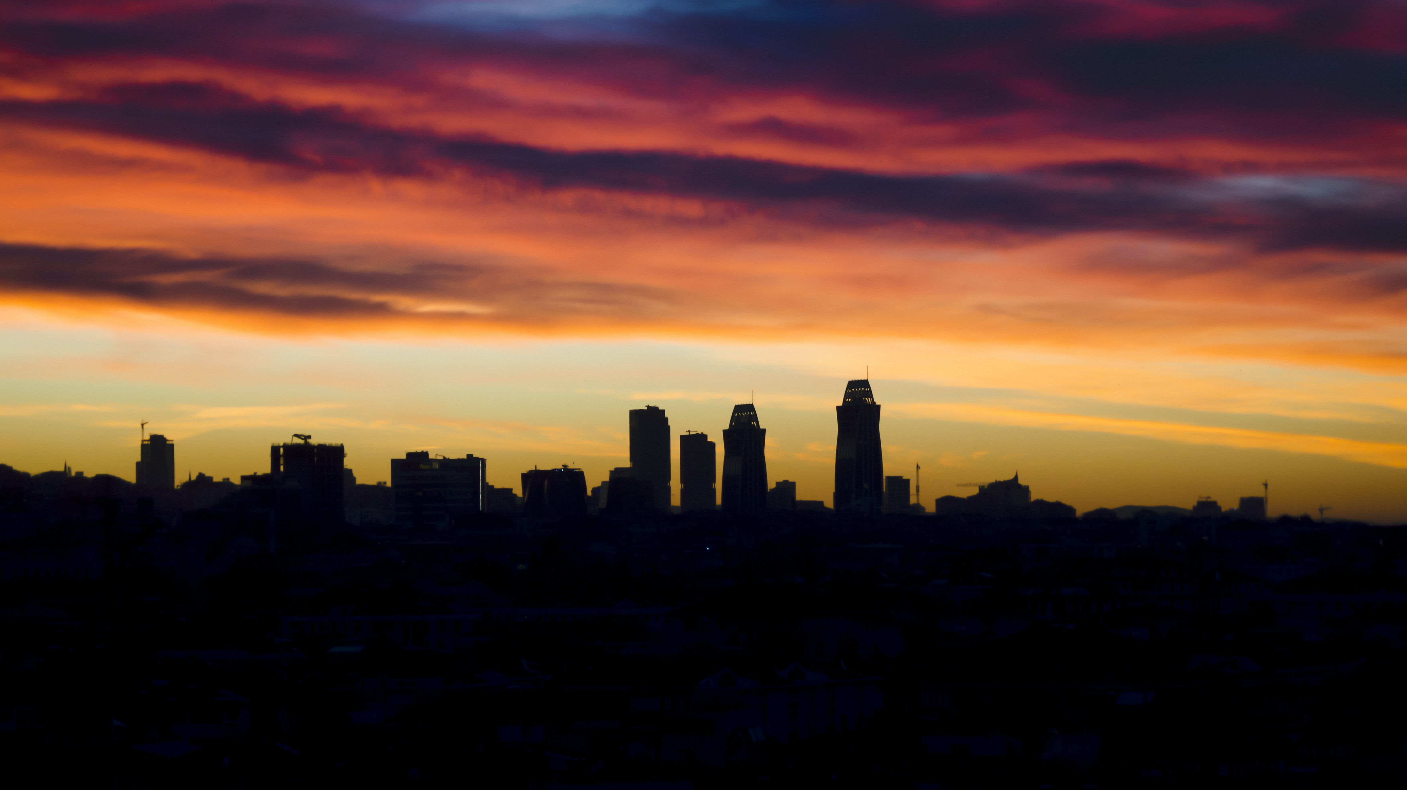 silhouette of buildings during orange sunset