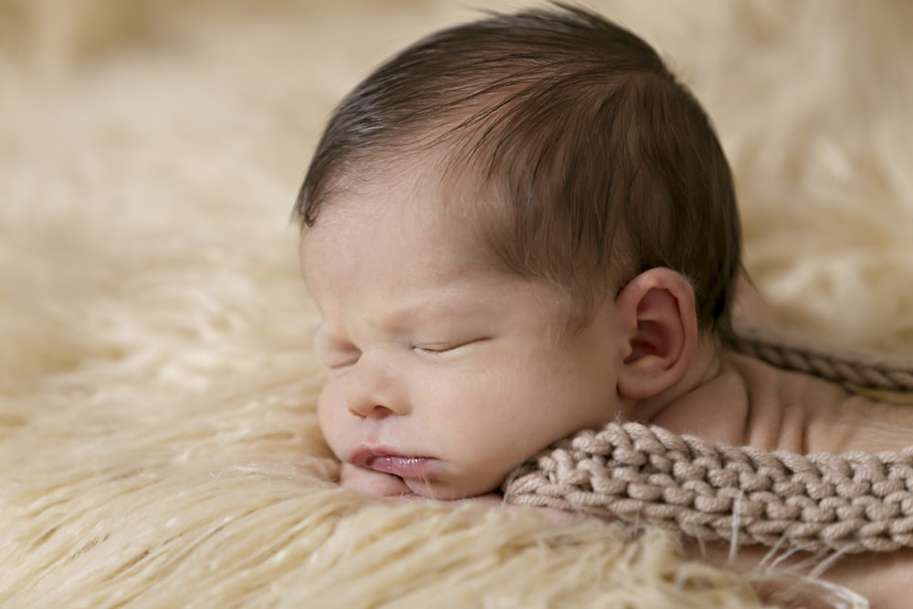 baby inside of beige and brown cloth