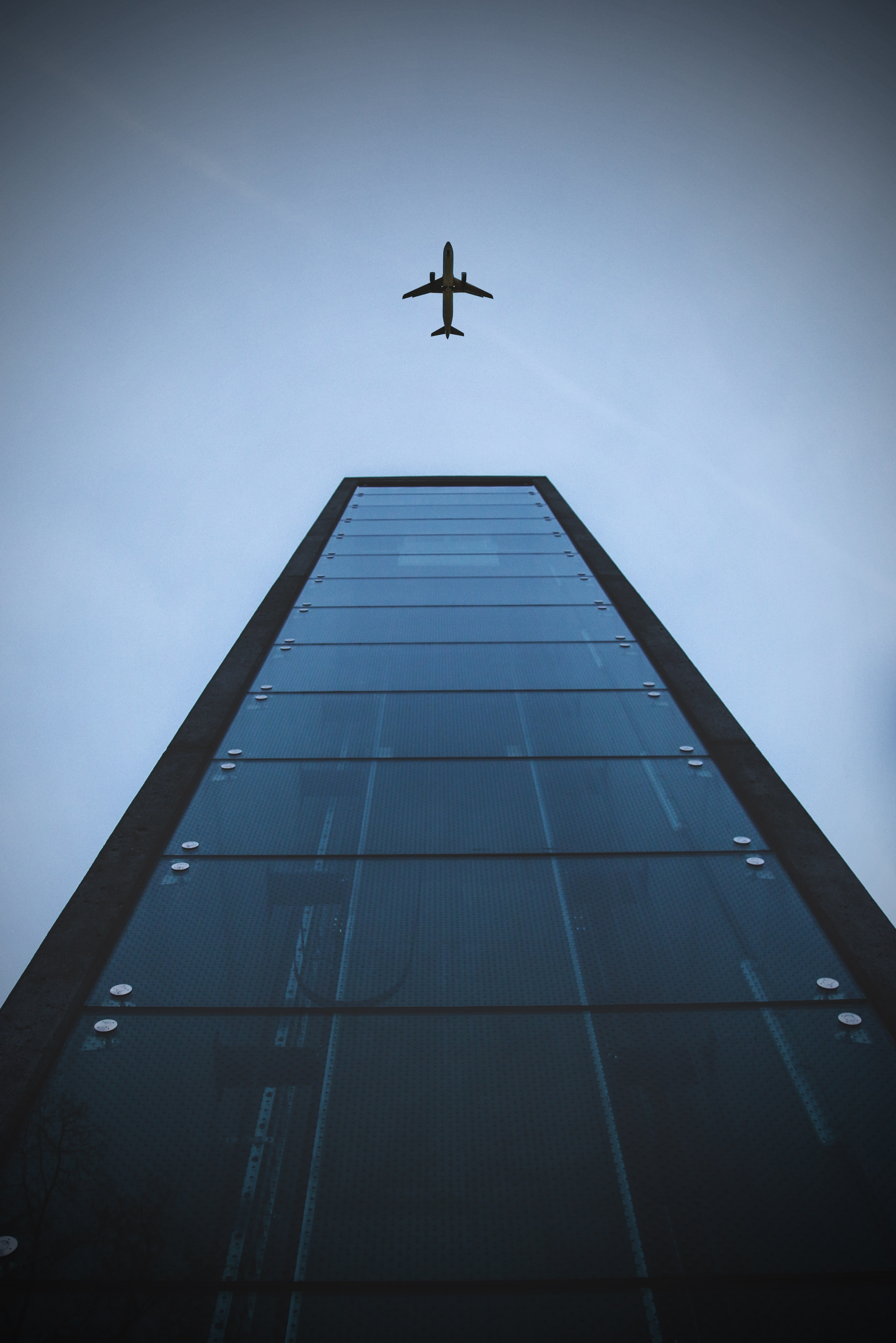 low-angle shot photography of building and airplane