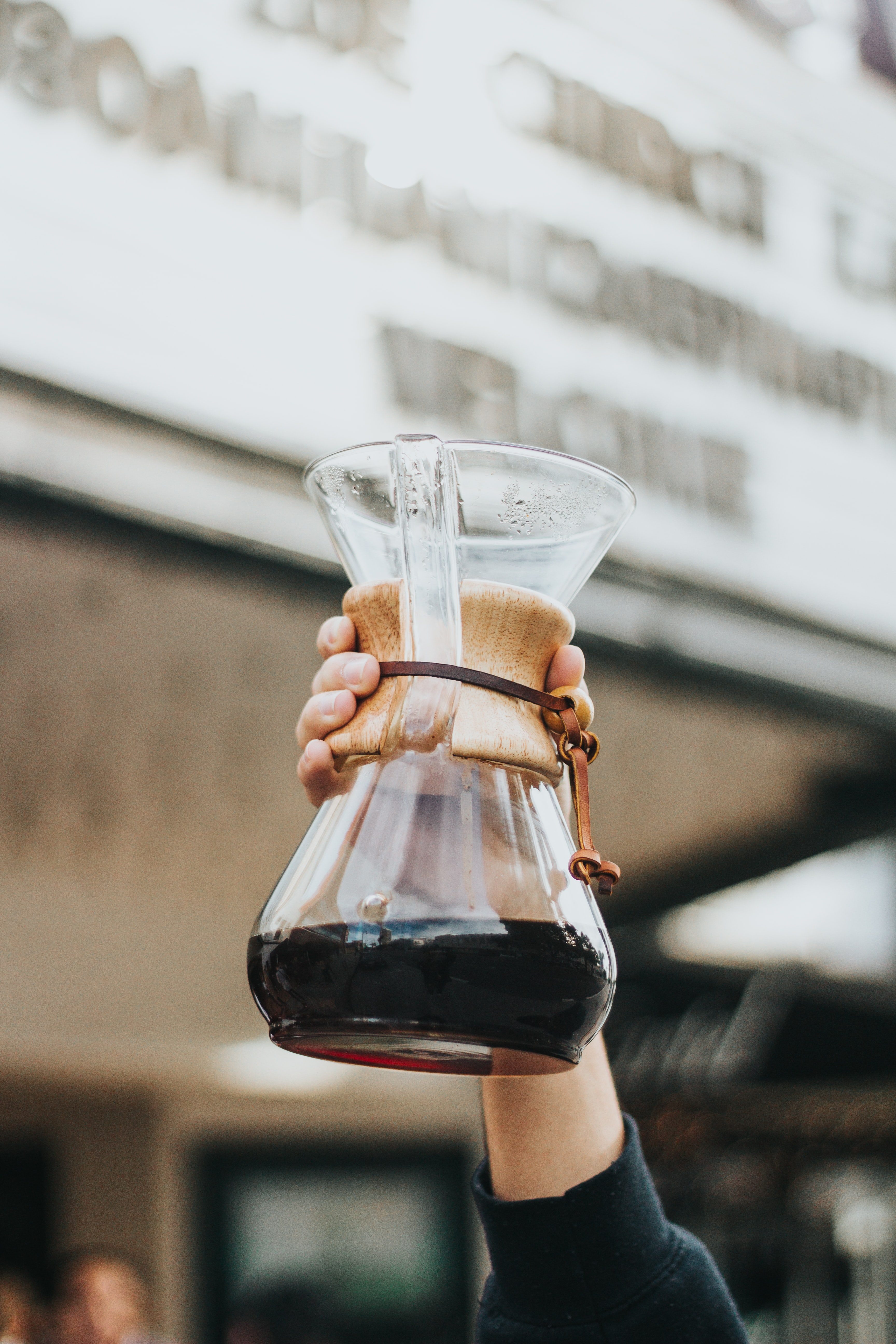 person holding clear glass coffee carafe