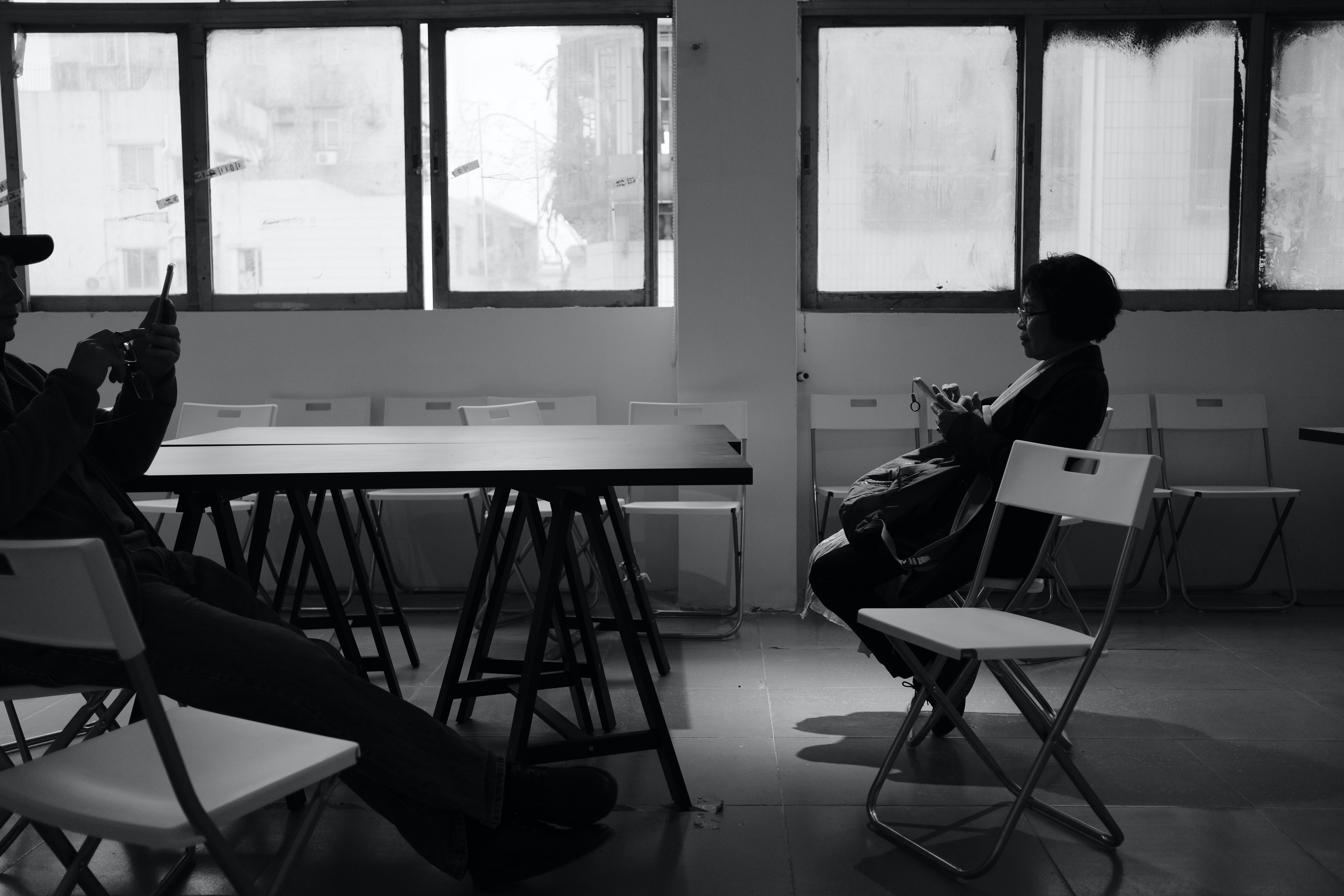grayscale photo of two person sitting on chair inside the room