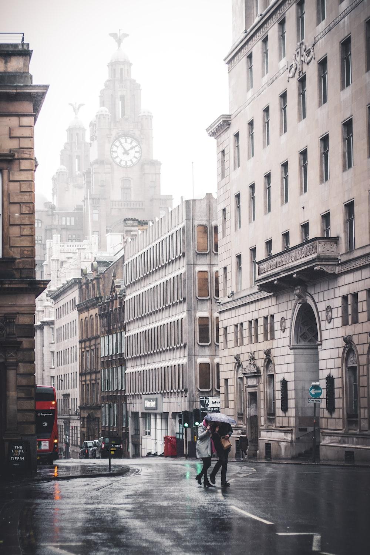 two person walking near concrete buildings