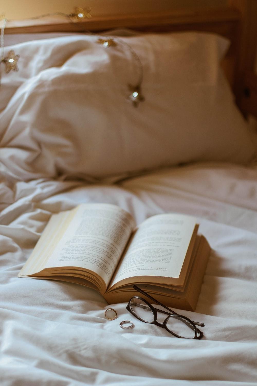 eyeglasses beside book and rings
