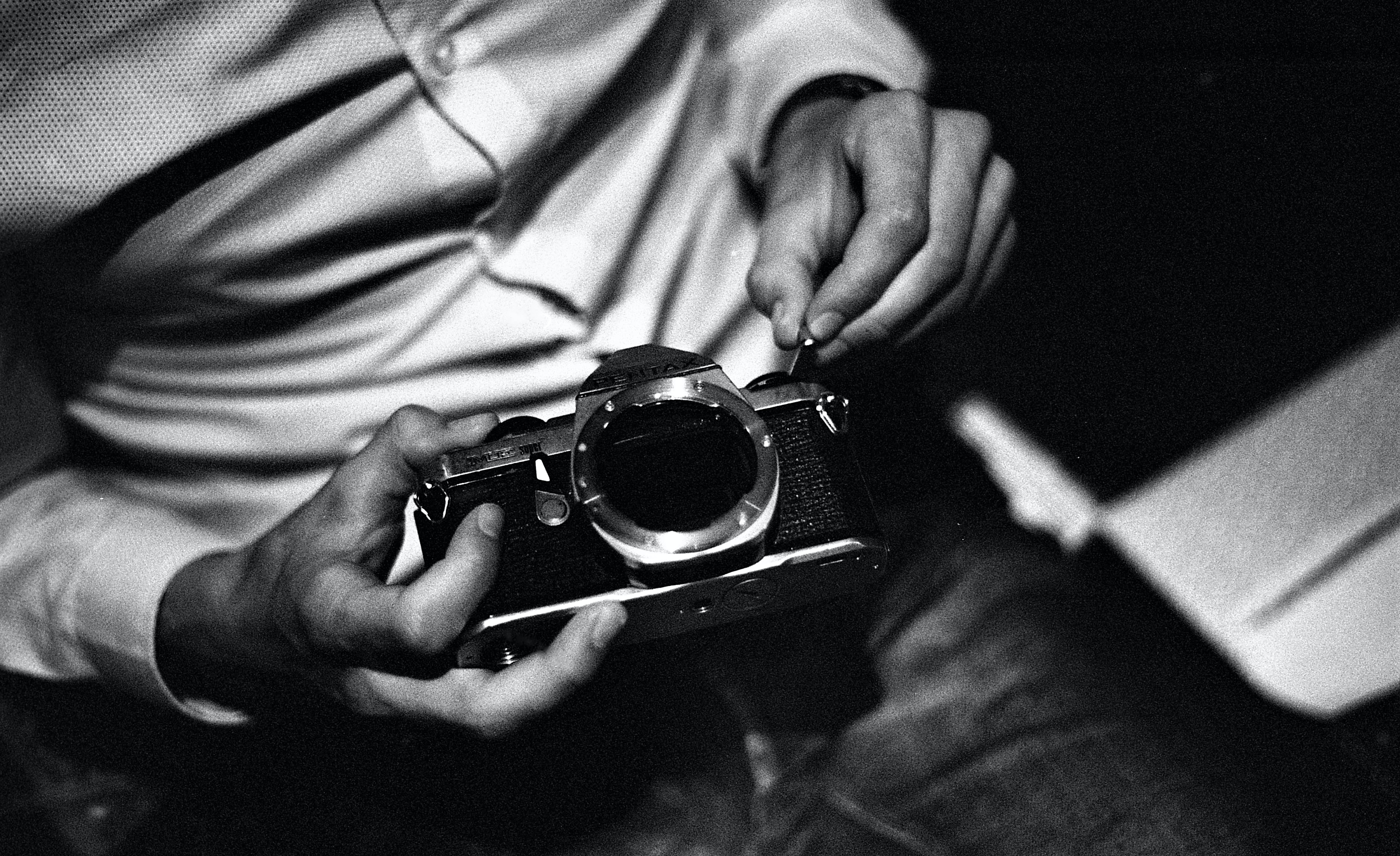 grayscale photography of man holding camera