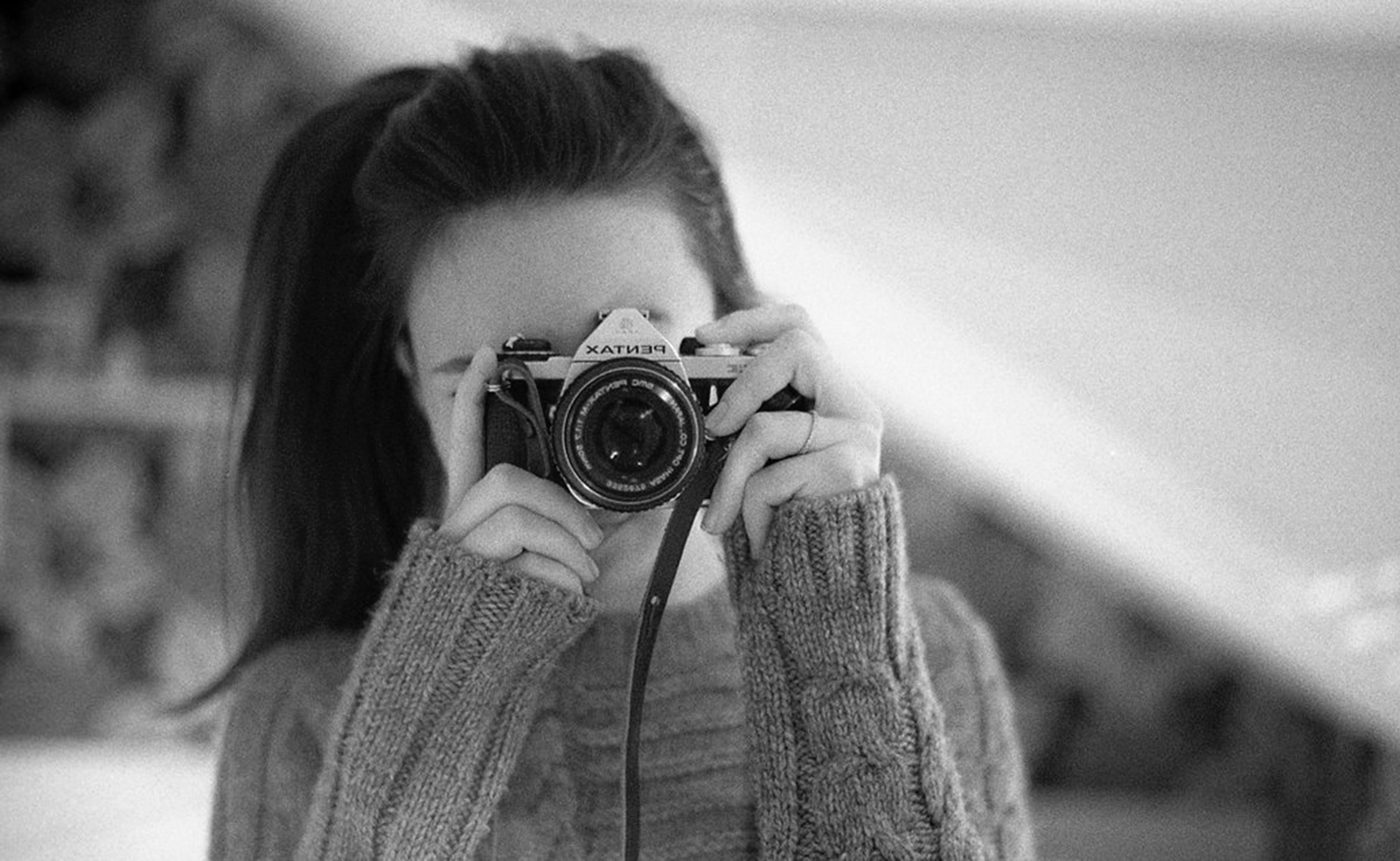grayscale photography of woman wearing long-sleeved shirt using camera
