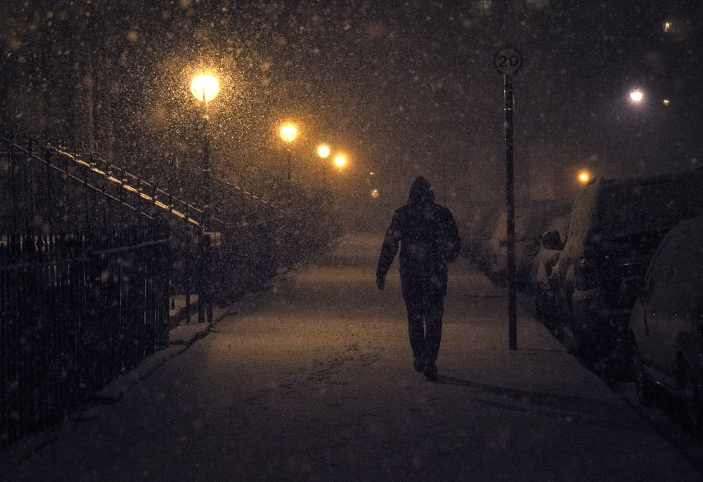 person walking at night with snow