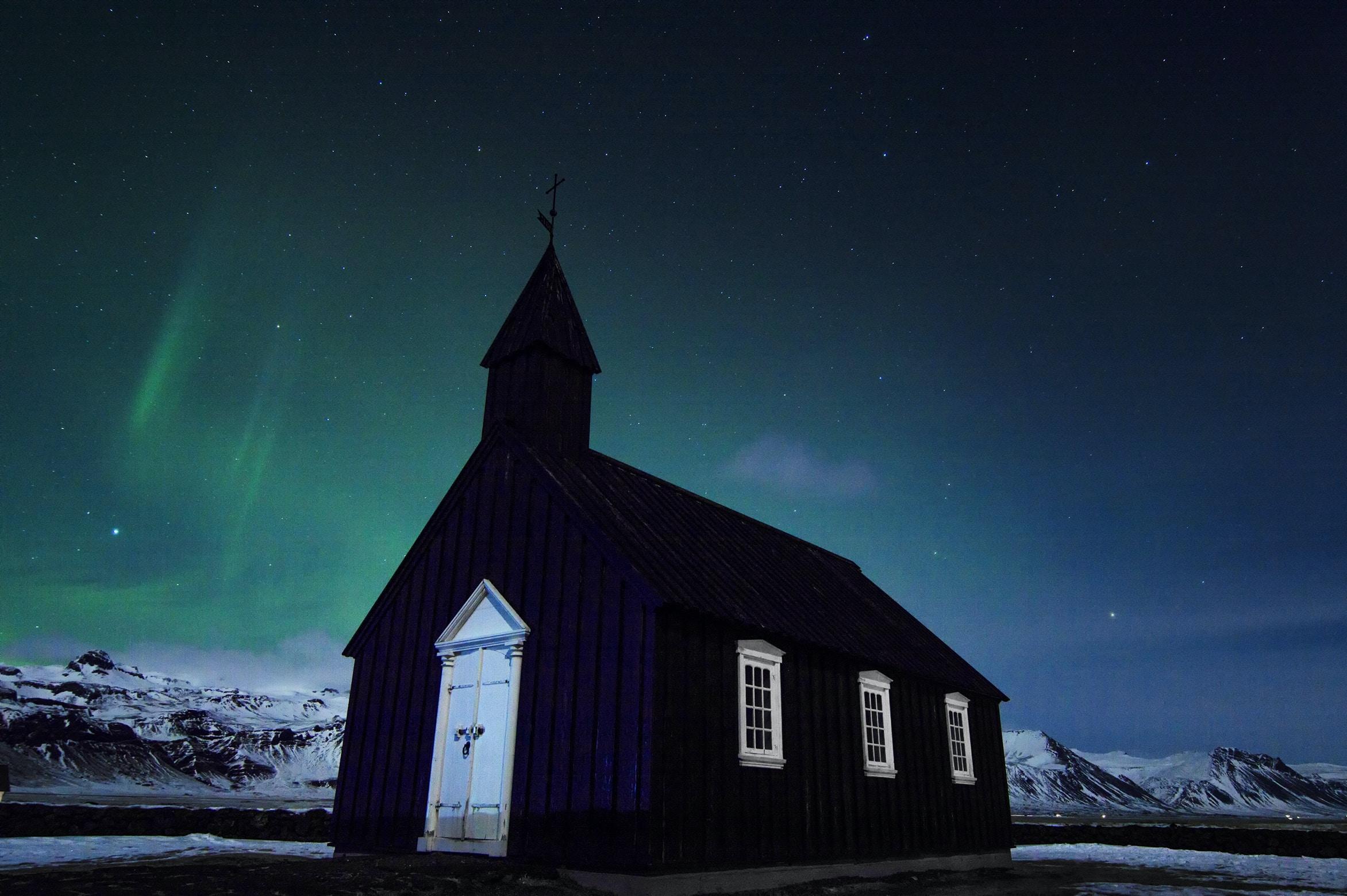 black church under northern lights at nighttime