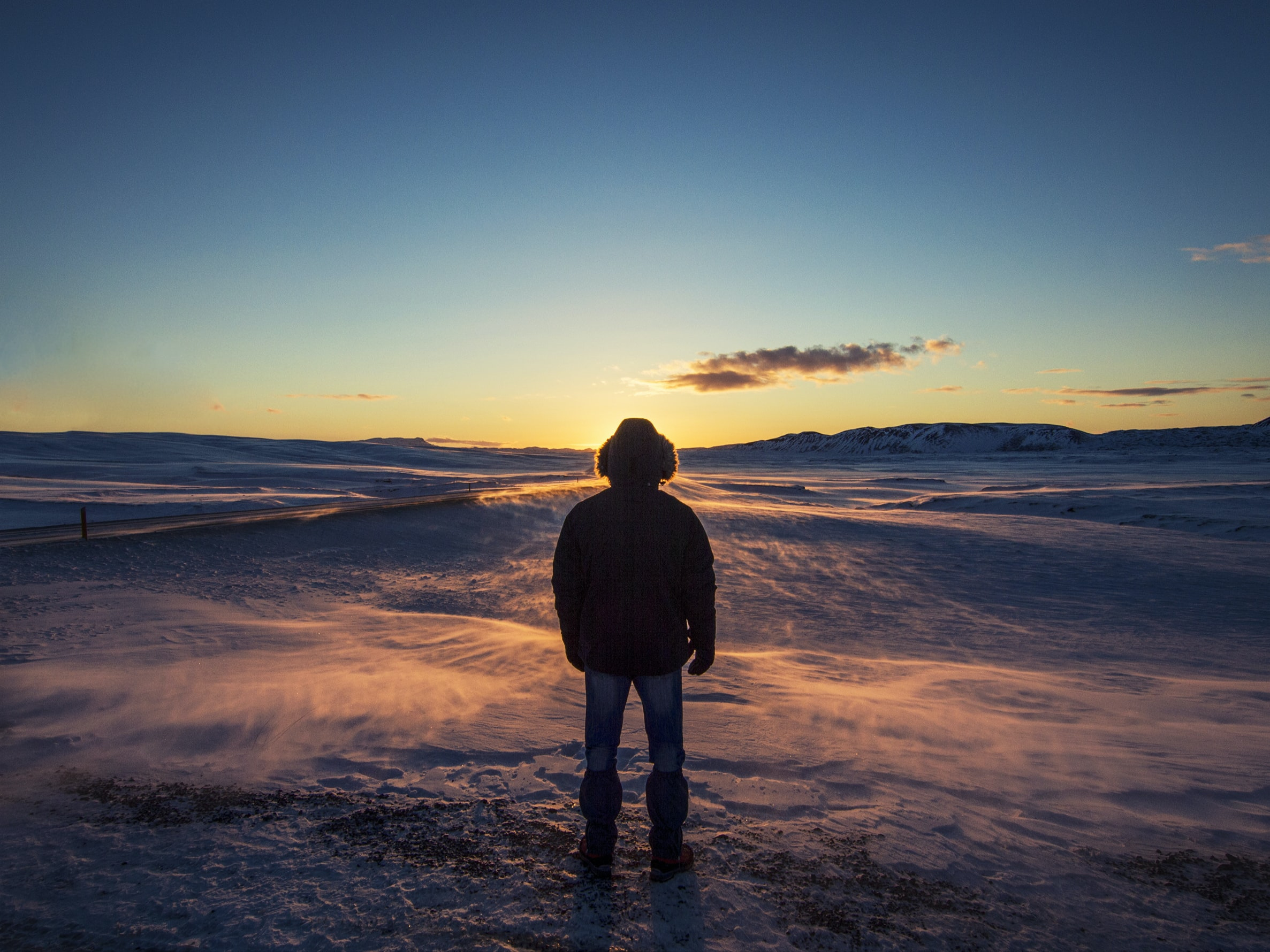 man standing on snow covered ground during sunrise