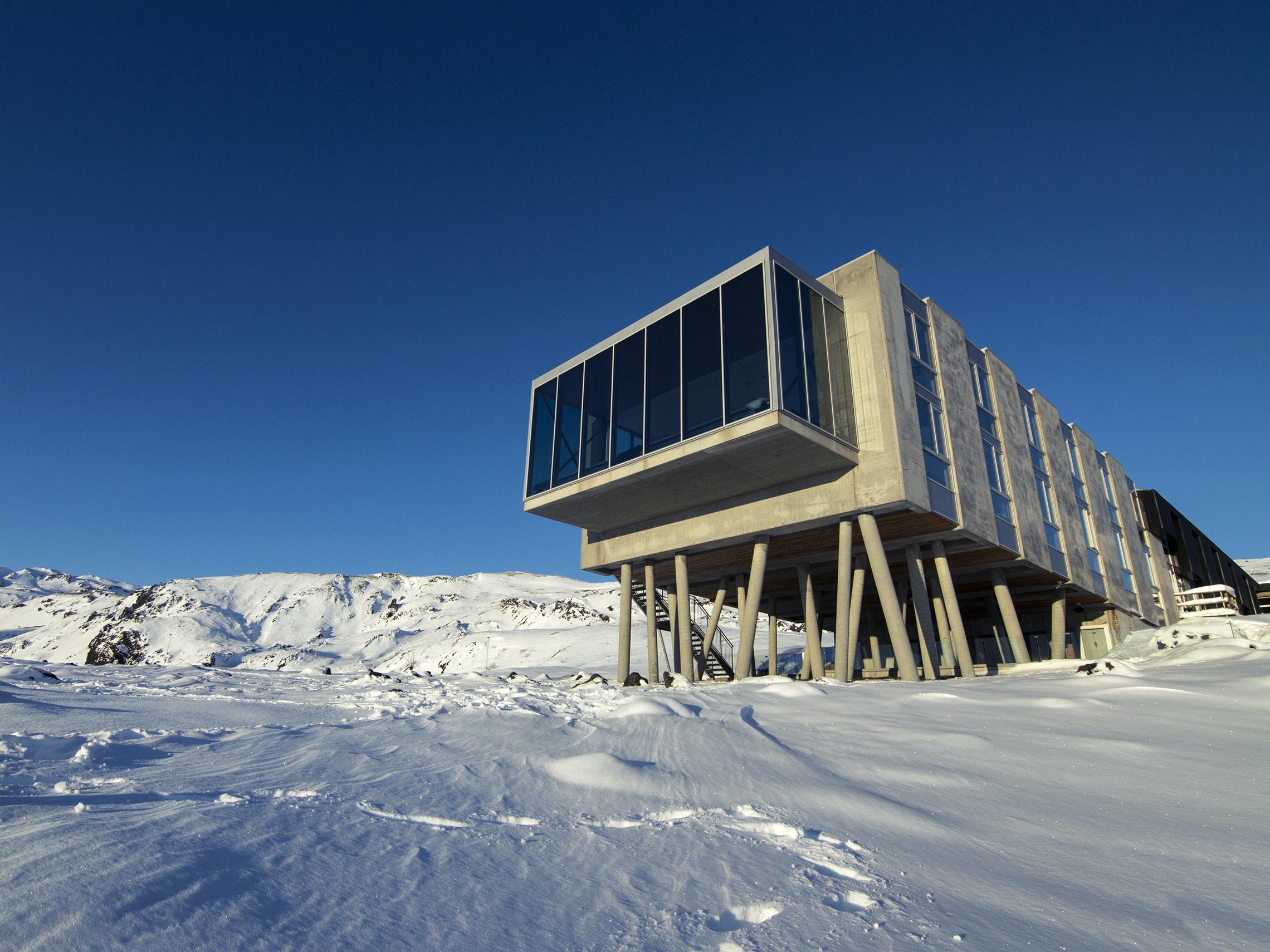 rectangular brown wooden organizer barn on snow covered mountain during daytime