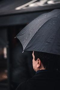 man wearing black top holding black umbrella walking near black awning