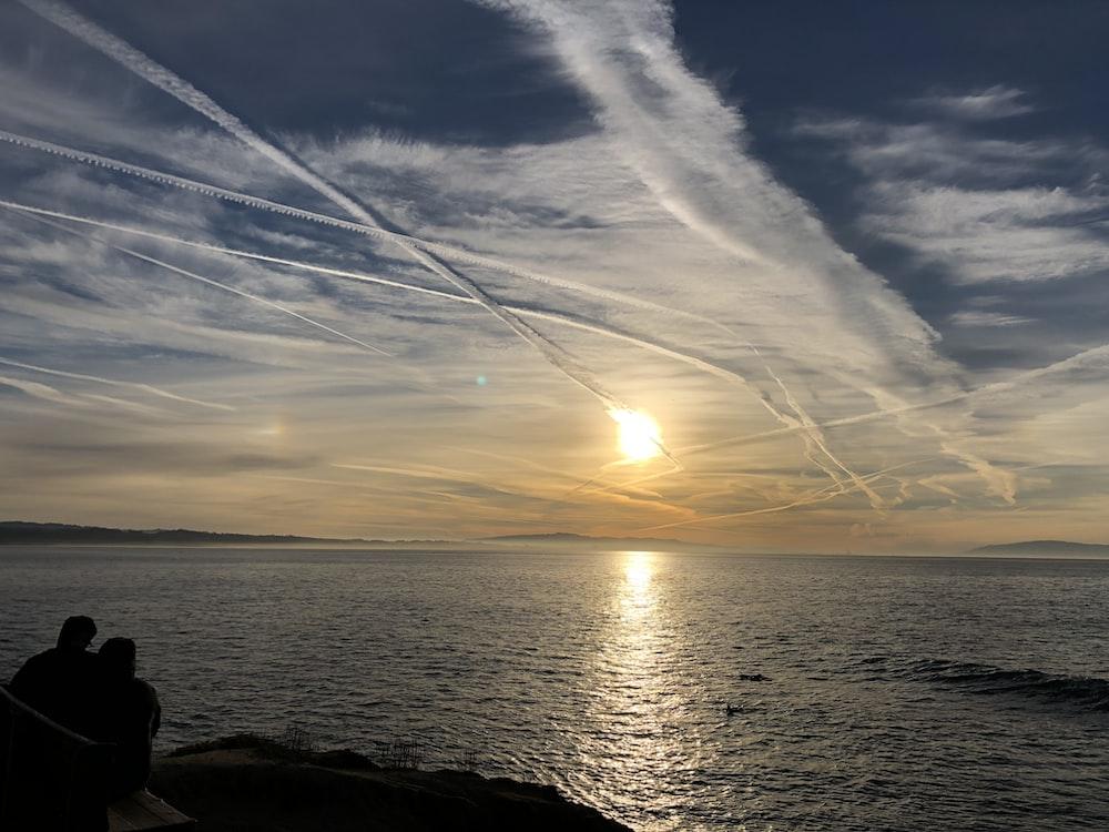 man and woman watching sunset near body of water