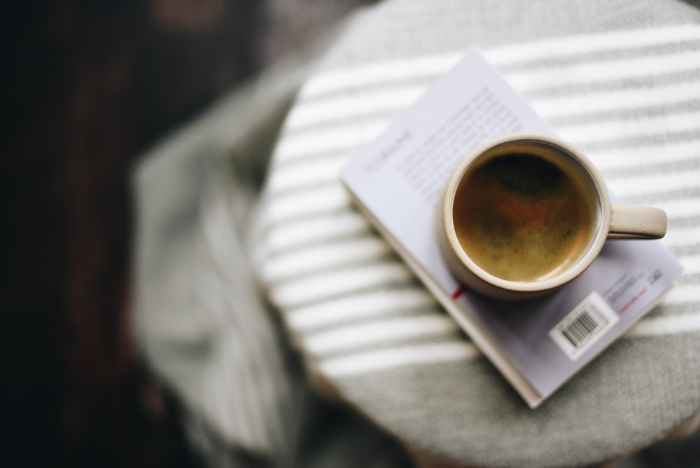 white ceramic mug with coffee on book